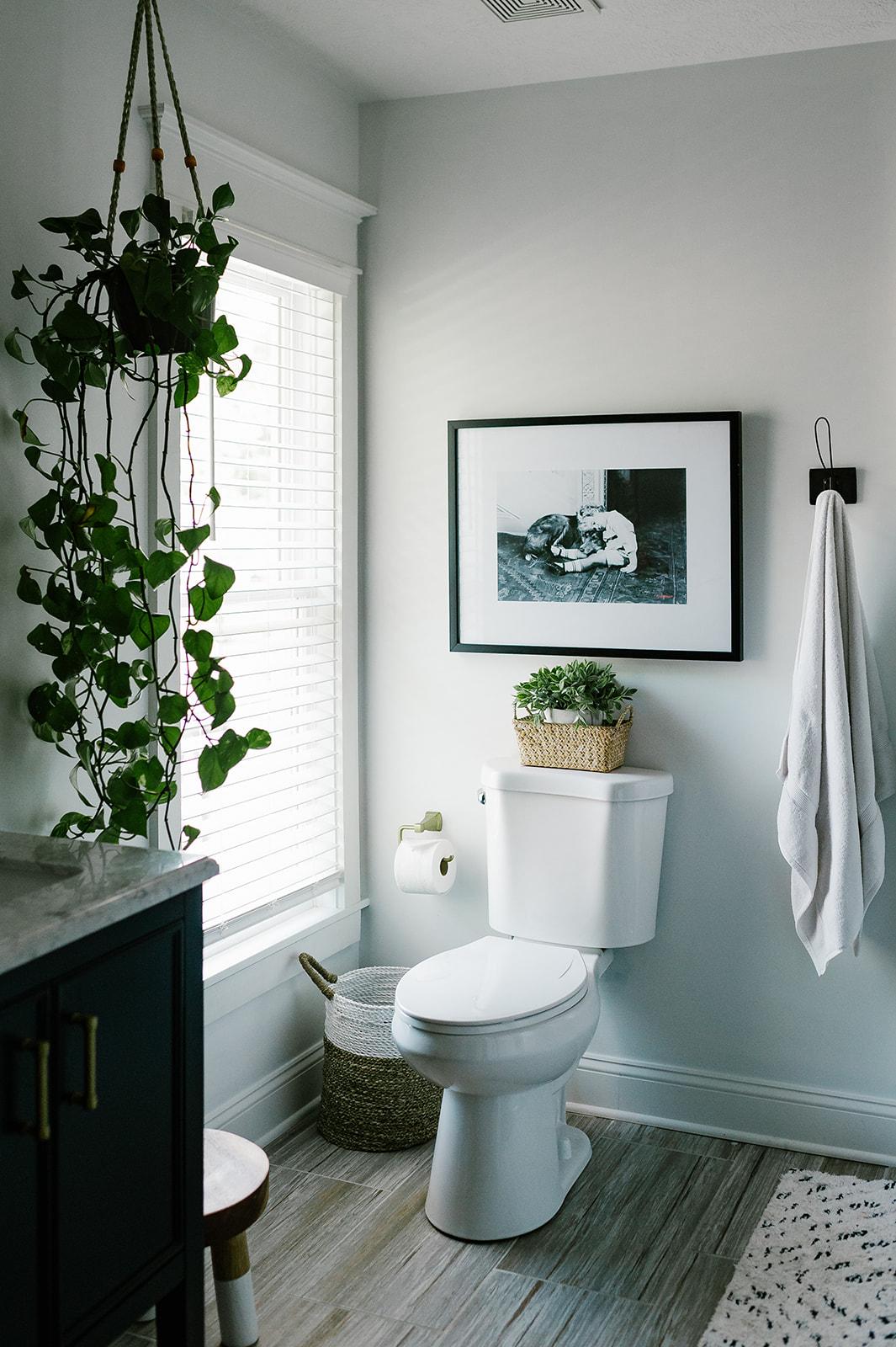 Our Bright & Boho Owner's Bathroom | Miranda Schroeder Blog  www.mirandaschroeder.com  White bathroom, navy blue double vanity with brass hardware, bathroom rug, Persian, wooden stool, storage, main bath, owner's bath